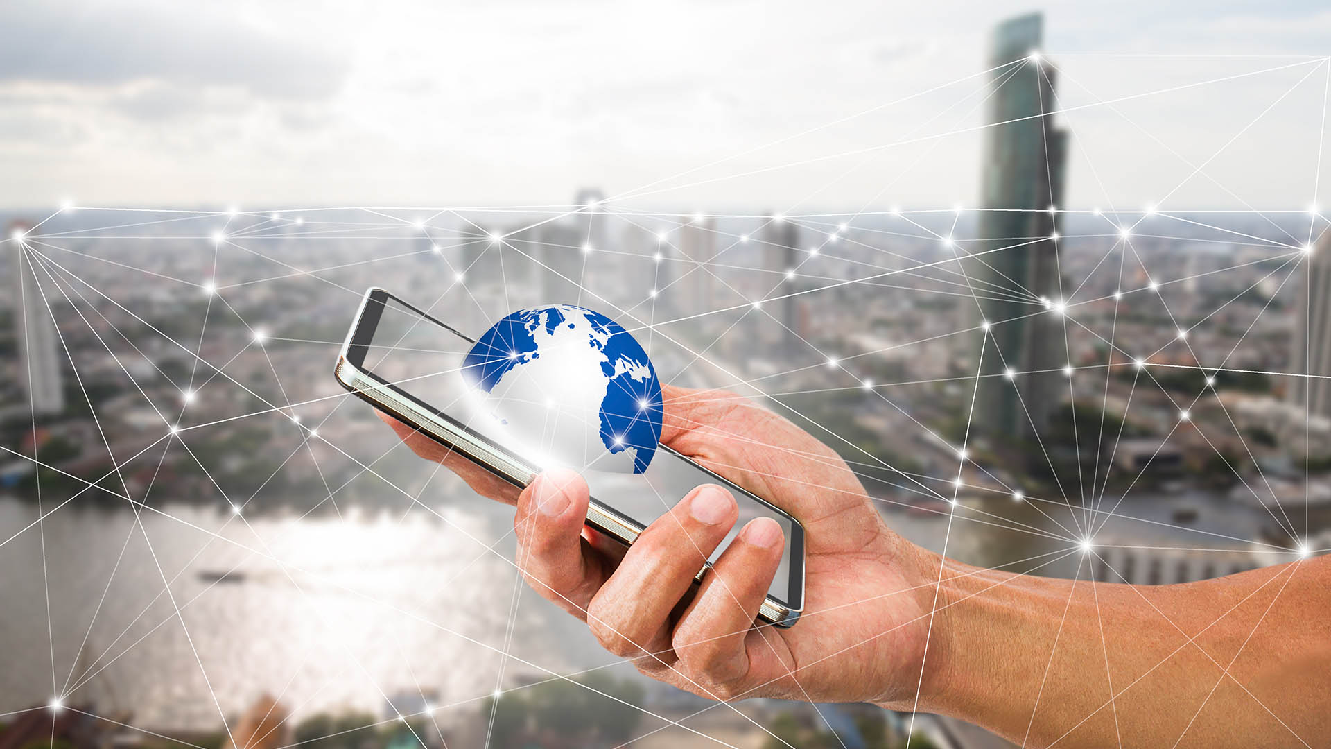 Man's hand holding mobile phone with globe on blurred city backg